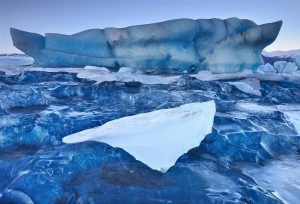 A small piece of frozen lagoon perched on top of a crystal blue iceberg.